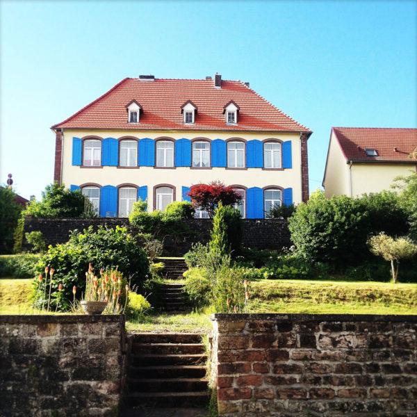 Kunterbuntes großes Haus frontal gesehen mit hellblauen Fensterläden und rotem Walmdach. Eine Treppe führt zwischen Sandsteinmauern auf das Gelände.