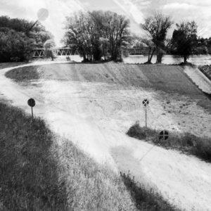Überlagerte, gespiegelte Schwarz-weiß-Aufnahme einer deutschen Flusslandschaft ohne Fluss mit Bäumen, Wiese, Deichauffahrt