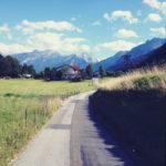 Blaustichig übersättigte Straßenszene einer offenbar bayerischen, ländlichen Dorfidylle mit Weg, der auf blaue Berge zuführt.