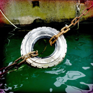 Ein Reifen an Kette über grünem Wasser vor einer Hafenmauer als Fender.