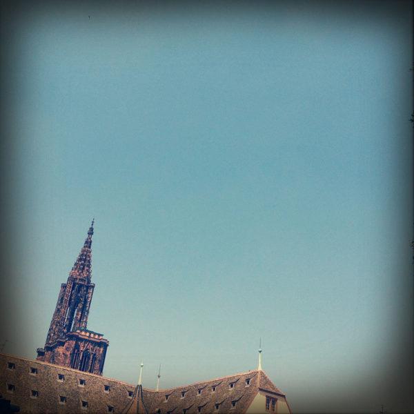 Viel Himmel im Bild und links im unteren Ecke fern ein spitzer Kirchturm etwas schräg