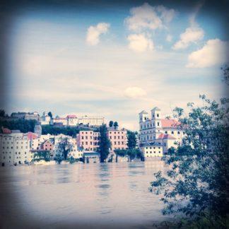 Blasses Retrobild über einen breiten Fluss hinweg auf eine städtische Uferbebauung blickend mit Zweigen im Vordergrund