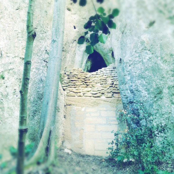 In verwachsenem, von Zweigen umranktem Felsloch klafft über einer mannshohen Vermauerung ein kleines Loch.