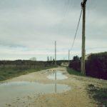 Ein verregneter Weg mit großen Pfützen, flankiert von einer Stromleitung.