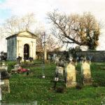 Zwei Gräber vorne und eine große Gruft vor Friedhofsmauer und kahlen Bäumen