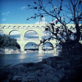 Hinter einem Gestrüpp erscheint ein altes römisches Aquädukt. Die Szene ist bläulich verfärbt.
