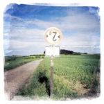 Als Durchfahrt-Verboten-Schild wurde an einem Landwirtschaftlichen Weg ein ehemaliges Maximal-2-Meter-breit-erlaubt-Schild verwendet- Die Landschaft zeigt Weite über Frühlinghaften Feldern, zerschnitten von schnurgeradem Weg.
