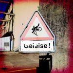 Warnschild mit stürzendem Radlerpiktogramm und der Unterschrift Geleise!