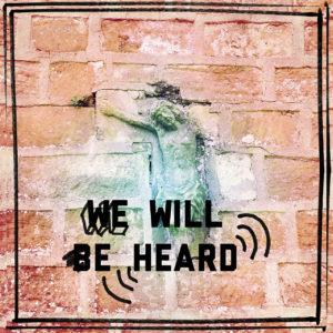 Eingemauertes Jesuskreuz in Sandsteinwand, mit Schriftzug We Will Be Heard.