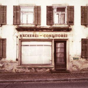 Geschlossener alter Einkaufsladen, Bäckerei - Conditorei. Heruntergelassener Fensterladen vor Schaufenster neben uralter Tür.