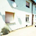 Schattenwurf einer Satellitenschüssel an weißer Hauswand eines Wohngebäudes.
