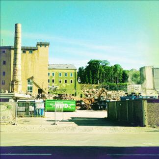 Baustelle eines im Abriss befindlichen Fabrikgeländes mit hohem Schlot.