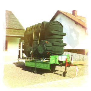 Grüner landwirtschaftlicher Anhänger, auf dem hochkant ein schwarzes Unterirdisch zu liegender Wassertank mit Gurten verzurrt ist. Die Bordwand des Anhängers ist heruntergeklappt. Das Bild hat einen gelblich grünen Farbstich.