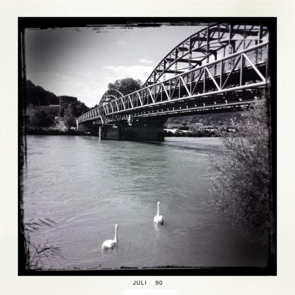 Schwarz-weiß-Aufnahme eines Flusses, auf dem im Vordergrund zwei Schwäne auf eine stählerne Fachwerkbrücke zuschwimmen, die den rechten Teil des Bilds als Kontrapunkt zum Wasser dominiert.