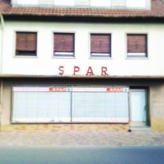 Die Fassade eines längst verlassenen Dorfladens (Spar). Jalousien hinter den großen Schaufenstern sind heruntergelassen.