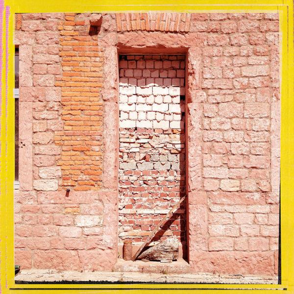Mit Kalksteinen vermauerte Tür in einer roten Sandsteinwand. Schräg steht ein Stock im Gewände