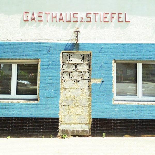 In hellblau gekachelter Wand ist eine Tür zwischen zwei Fenstern zugemauert. Über der Tür der Schriftzug Gasthaus Stiefel.