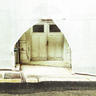 Die verhangene Tür einer Hausbaustelle hinter einem Gerüst ist zugänglich wie durch einen Bühnenvorhang