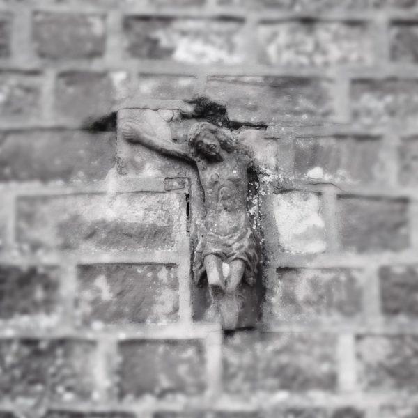 In eine Bruchsteinmauer ist ein halbes Jesuskreuz als Baustein integriert. Nur Kopf, Beine bis zum Knie und der rechte Arm sind noch erhalten.