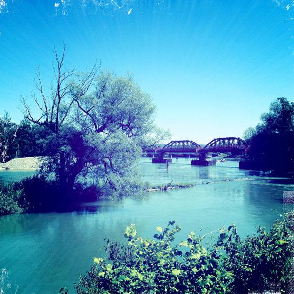 Flussaue bläulich verfärbt mit Blick auf eine Eisenbahnbrücke aus Stahlfachwerk und eine kleine Insel mit Weidenbaum.