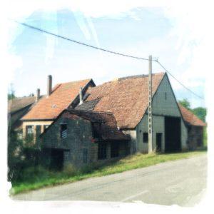Ein altes Bauernhaus mit krummem, abgesacktem, aber intaktem Dach.