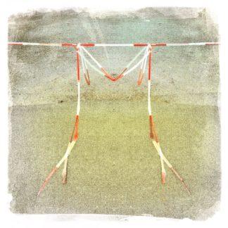 Ein Absperrband hängt quer von einem Parkplatz und wie an einer Leine aufgehängt bilden Reste des Absperrbands den Buchstaben M