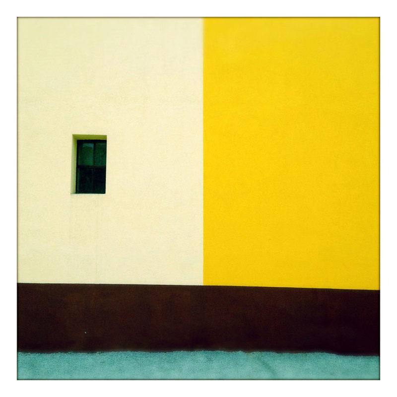 Dreiteilig rechtwinklig gefärbte Fassade. Links oben weiß mit Fenster, rechts oben gelb, unten zwei Streifen scharz und hellblau.