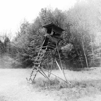 Schwarz-weiß-Bild eines schräg gebauten Hochsitzes im Profil. Eingang und Leiter zeigen nach links. Im Hintergrund Wald. Das quadratische Bild ist nach den Ecken zart abgeblasst vignettiert bis ins Weiß.