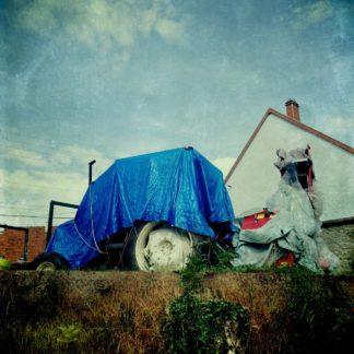 Mit blauer Plane verdeckt steht ein Traktor vor dörflichem Wohnhaus. Das Bild ist Underfoot aufgenommen an einer dürr bewachsenen Böschung