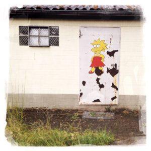 Eine weiße Tür in einer Baracke, auf der eine Lisa Simpson-Figur gemalt ist.