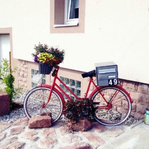 Dekofahrrad, rot mit Blumenampel am Lenker, der nach links zeigt. Vor einem Wohnhaus.