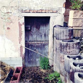 Mit einem Stock verbarrikadierte Stalltür in einer alten Bauernhausmauer. Vor der Tür stehen Kübelpflanzen