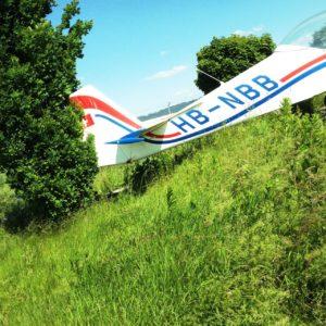 Schräg fotografiertes Heck eines Sportflugzeugs auf grüner Wiese. Die Oberfläche liegt diagonal von links unten.