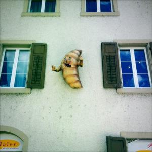 An einer Hauswand zwischen zwei Fenstern mit grünen Läden hängt ein personifiziertes, lachendes Croissant mit kleinen Ärmchen gestikulierend.