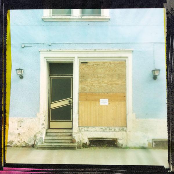 Mit Spanplatten verbaute Fassade eines offenbar ehemaligen Ladenschaufensters. Daneben eine Tür mit Gitterglas. Die Hauswand hat eine türkis-graue Farbe.