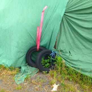 Eine grüne Plane auf einem offenbar Silo ist mit zwei Autoreifen befestigt, die an rosa Bändern hängen.