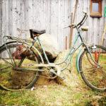 Ein altes Fahrrad, das auf dem quadratischen Bild im Profil vor einer Holzbretterwand steht und dessen Reifen vorne und hinten nicht mehr ganz aufs Bild gepasst haben.