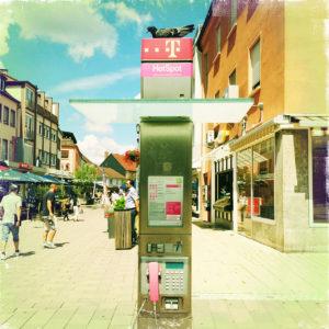Auf einer Telefonsäule der Telekom in einer mäßig belebten Innenstadtszene sitzt eine Taube.