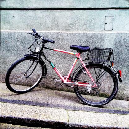 Ein Fahrrad mit Korb auf dem Gepäckträger lehnt an einer Hauswand. Die Straße ist steil ansteigend von rechts nach links.