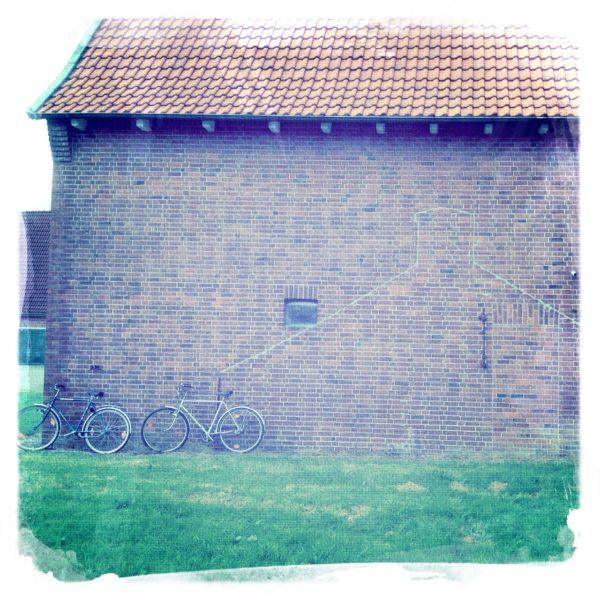 Flächiges Bild mit blassem Grün unten, violett-grauer Wand darüber und blassem Ziegeldach ganz oben. An der Wand lehnen unscheinbar zwei Fahrräder