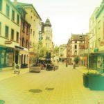 Eine recht leere Fußgängerzonenszene mit gelblich verfremdeter Verfärbung. Mischbauten der Nachkriegszeit und wenige alte Häuser.