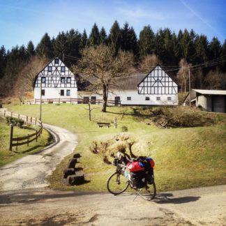 In ländlicher, hügeliger, von hohen Nadelbäumen gesäumter, dennoch offen wirkender Idylle steht ein bepacktes Reiserad vor der Zufahrt zu zwei einzelstehenden weißen Fachwerkbauten.
