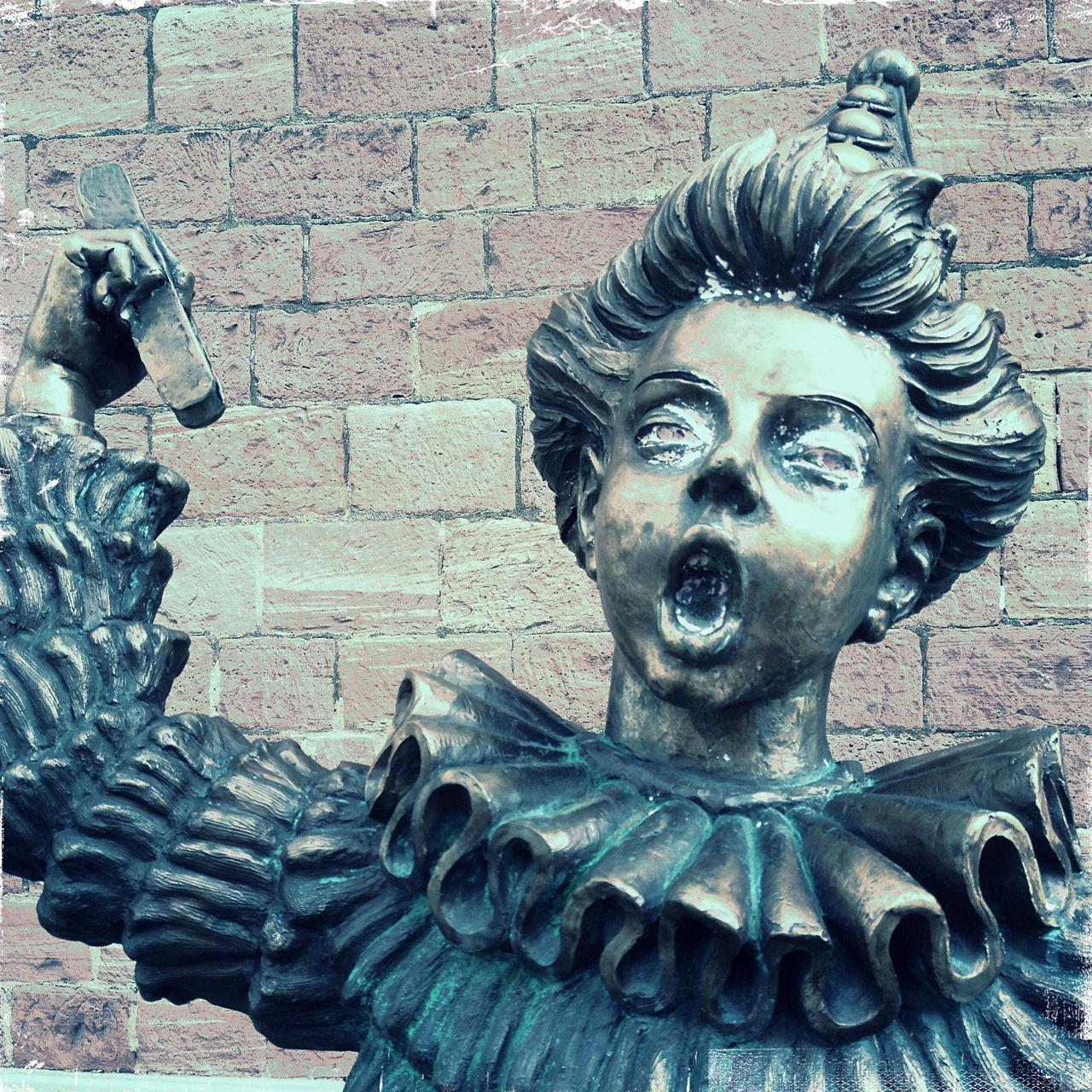 Oberkörper und Kopf einer Skulptur mit wallendem Gewand und gewelltem, großem Kragen vor eine blass-lila-braunen Sandsteinwand. Der Jüngling scheint laut zu singen, hat den Mund zum O geformt und reckt seinen rechten Arm.