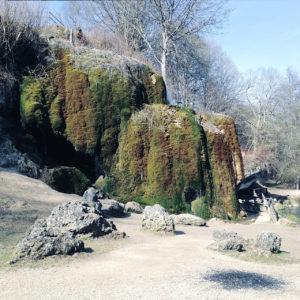 Fehlfarbenbild eines völlig mit Moos überwucherten mehrere Meter hohen geologischen Objekts, das sich auf einer freien Fläche zwischen Felsbrocken ersteckt und im Bild kaum als Wasserfall zu erkennen ist, da das Wasser zwischen Moos rinnt.