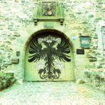 Ein grünlich verfärbtes, zartblasses Portal mit Rundbogen und großem Wappen auf den beiden Flügeln des Tores. Ein stilisierter Adler.
