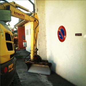 Vor weißer Hauswand mit Parkverbotsschild steht ein kleiner gelber Bgger mit heruntergelassenem Arm wie ein Mensch in einer Schmollecke