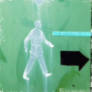 Ein Mann-Piktogramm, nach rechts gehend auf grünlichem, kaum strukturiertem Hintergrund neben einem fetten schwarzen, etwas angefledderten Pfeil nach rechts.