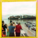 Eine handvoll Menschen mit dem Rücken zum Betrachter auf einer offenbaren Fähre, an der ein Containerschiff vorbeifährt. Die Menschen fotografieren das Containerschiff. Das quadratische Bild hat einen gelben Rand.