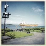 Videoüberwachungsmast vor einem Meeresarm. Im Hintergrund ein großes Frachtschiff.