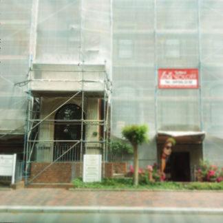Eingerüstetes Haus mit Netzen verhüllt. Nur zwei Türen sind zu sehen, wovon die linke auf einer Treppe liegt, die rechte ganz klein in einem Kellerloch.
